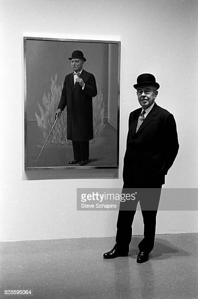 Painter Rene Magritte in front of one of his paintings