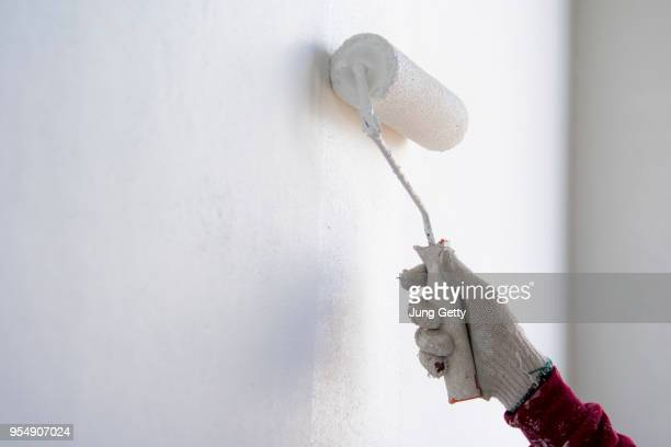 painter roller by construction worker in new cement wall - wall building feature stock pictures, royalty-free photos & images