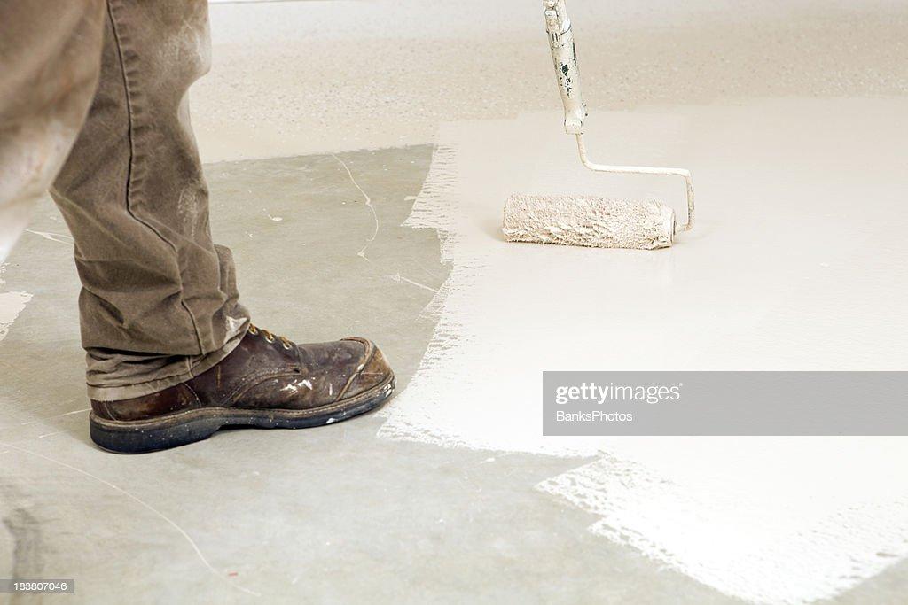 Painter Rolling Epoxy Paint on Concrete Floor : Stock Photo