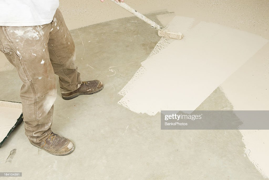 Painter Rolling Epoxy Paint on Concrete Floor : Stock Photo