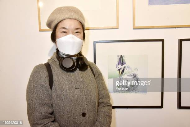 """Painter Rong Guo poses with her work during """"Antidotes"""" Collective Exhibition at Espace des Femmes on March4, 2021 in Paris, France."""