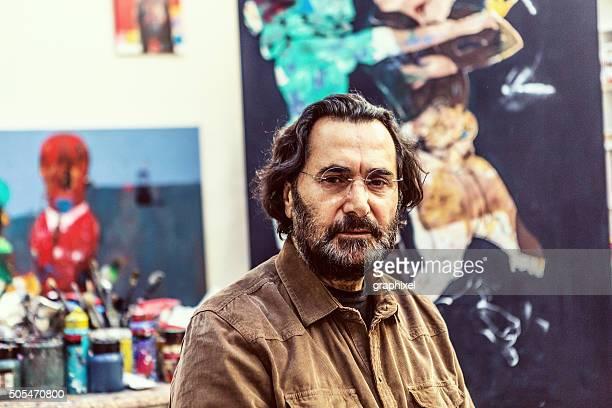 Homem sentado na frente de Cavalete de arte Sudio