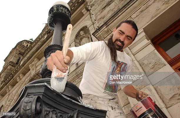 Painter Troy Mason paints a lamp post at the British Columbia Parliment building October 4 2002 in British Columbia Victoria Canada Mason is painting...
