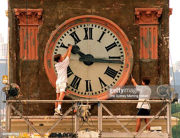 Painter Wayne Fleming of Minchenbury working on the Balmain Post Office Tower clock playfully trys to stop time while coworker David Hamilton works...