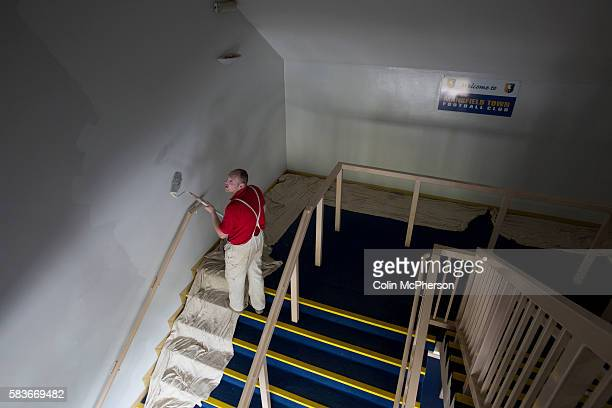 Painter working on one of the interior stairwells at Mansfield Town's Field Mill stadium during an open day held for the club's supporters as the...