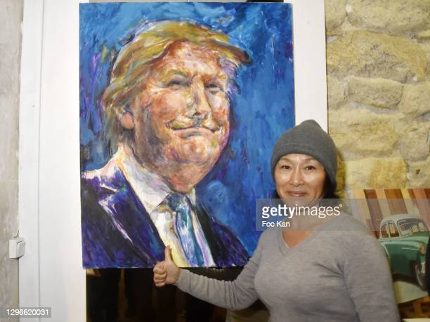 """Painter Xiuyi Shen poses with a portrait of president Donald Trump during """"Voyages Au Pluriel"""" Preview at 24 Rue De Lappe on January 15, 2021 in..."""