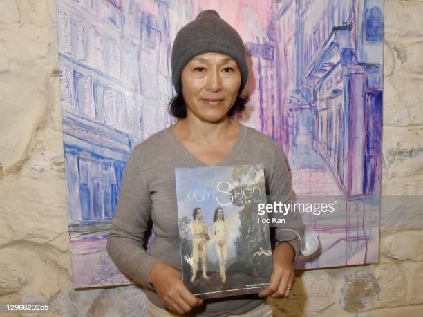 """Painter Xiuyi Shen poses with her book with French president Nicolas Sarkozy and Carla Bruni portrayed on the cover during """"Voyages Au Pluriel""""..."""