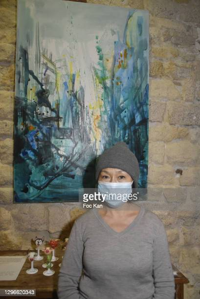 """Painter Xiuyi Shen poses with her work during """"Voyages Au Pluriel"""" Preview at 24 Rue De Lappe on January 15, 2021 in Paris, France."""