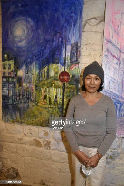 """Painter Xiuyi Shen poses with their work during """"Voyages Au Pluriel"""" Preview at 24 Rue De Lappe on January 15, 2021 in Paris, France."""