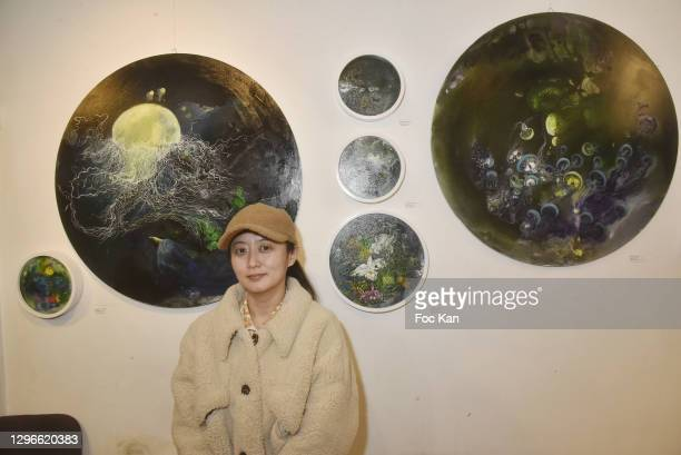 """Painter Zhu Wenyu poses with their work during """"Voyages Au Pluriel"""" Preview at 24 Rue De Lappe on January 15, 2021 in Paris, France."""