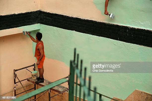 Painters apply a fresh coat of green to a basement level courtyard January 20 2015 in Havana Cuba Officials from the Cuban and United States...