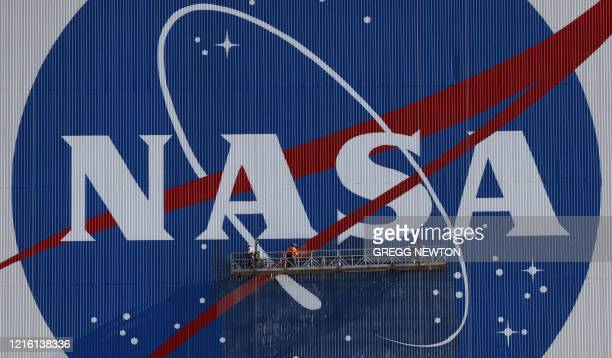Painters refurbish the NASA logo on the Vehicle Assembly Building at the Kennedy Space Center in Florida in Florida on May 29, 2020. The faded...