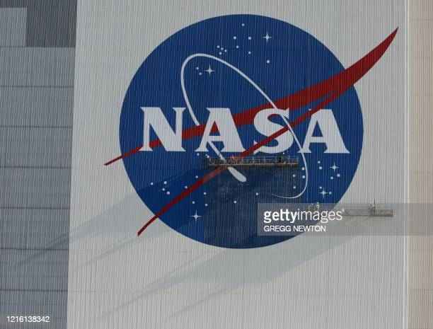 Painters refurbish the NASA logo on the Vehicle Assembly Building at the Kennedy Space Center in Florida in Florida on May 29 2020 The faded...