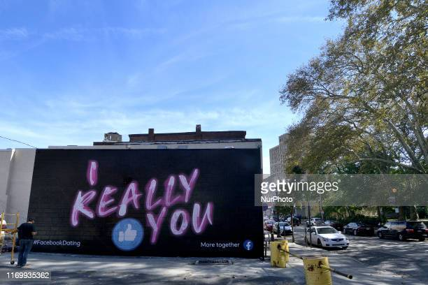 Painters work on an advertisement for the Facebook dating service on a sidewall in the Germantown neighborhood of Philadelphia, PA., on September 20,...