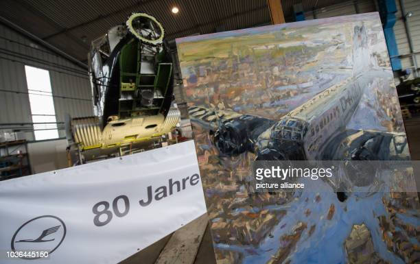 A painting by artist Hinnerk Bodendieck depicting the Junker Ju 52 standing in front of the real plane in a hall on the grounds of LufthansaTechnik...
