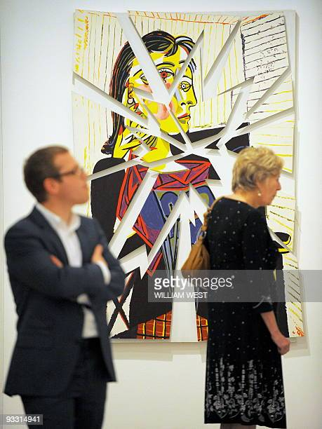 A painting by Maria Kozic looks down on two people inspecting an exhibition titled Cubism Australian Art at the Heide Museum of Modern Art a major...