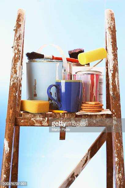 Painting equipment and mug on stepladder, close-up