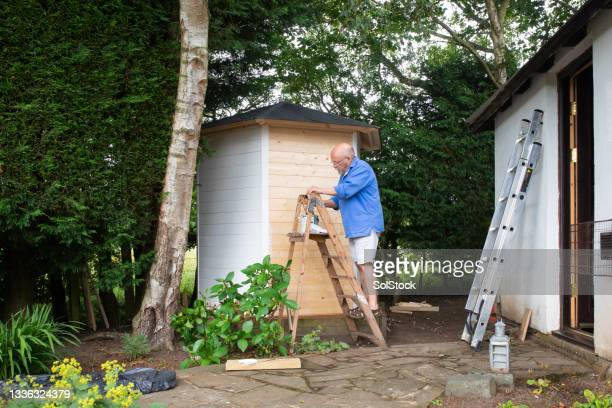 painting garden outhouse - working seniors stock pictures, royalty-free photos & images