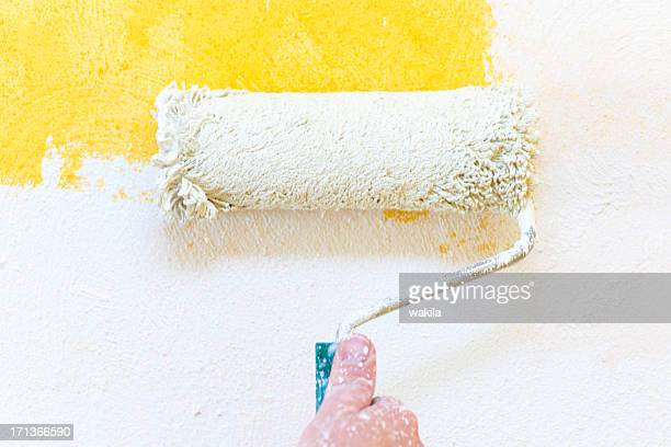 painting hand with paintbrush yellow and white