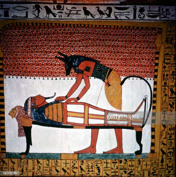 A painting in the tomb of SennedjemA priest wearing the mask of Anubis the jackal headed god of embalming leans over a mummy in its anthropoid coffin...