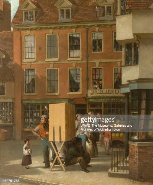 Painting of a cobbled street with red shops in the background, A group of figures stand in line behind a box on a wooden stand, To the right of the...