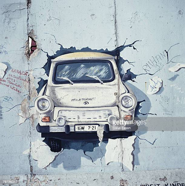 A painting of a Trabant car bursting through a wall in post unification Berlin August 1993
