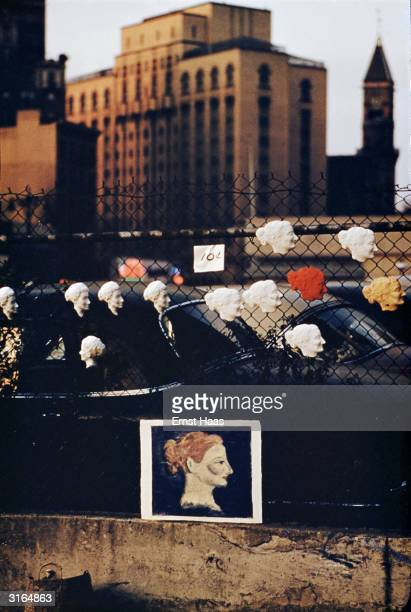 A painting of a woman in profile and a set of matching cameos displayed for sale on a fence New York City circa 1955 The cameos are priced at 10...