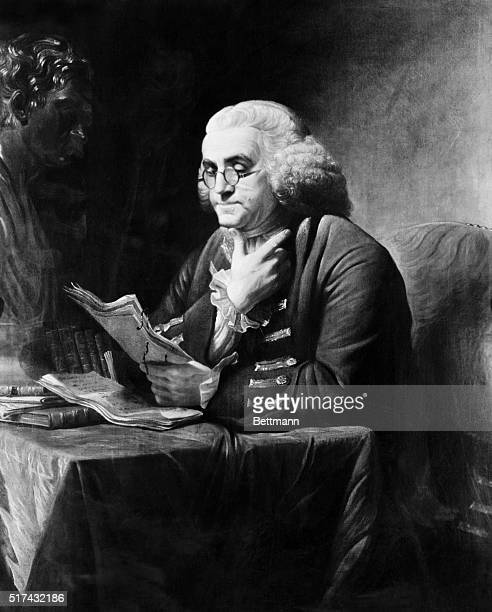 Painting of American statesman and founding father Benjamin Franklin seated at his desk reading papers