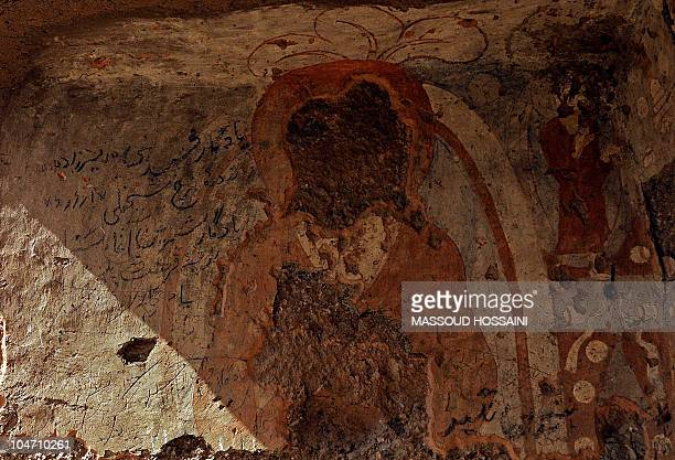 A painting of Buddha which was damaged by the Taliban is seen at the top of a cave's entrance in Bamiyan on October 15 2008 at the cavemonasteries of...