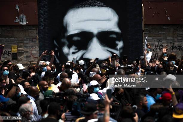 A painting of George Floyd stands behind a group of people gathered at a memorial on the block where he was killed by police on June 2 2020 in...