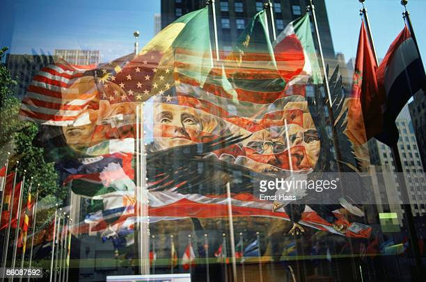 A painting of Mount Rushmore and an American Eagle combined with a reflection in a window of the Rockefeller Centre and the various flags outside the...