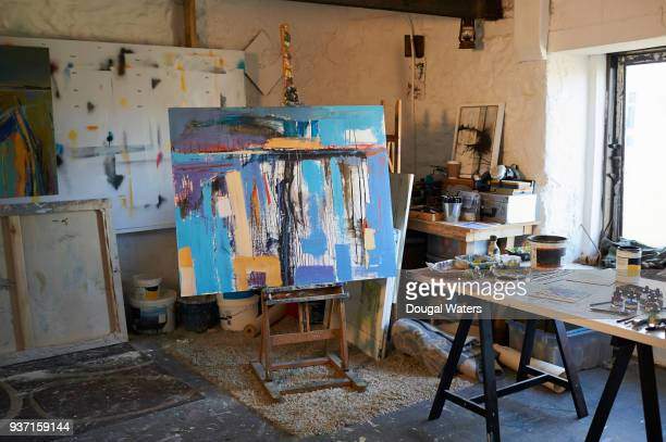 painting on easel in artist studio. - arte foto e immagini stock