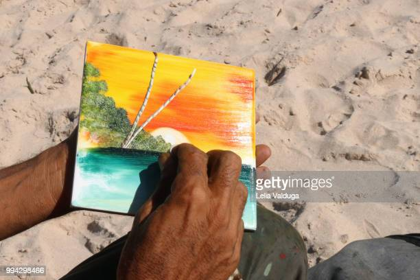 Painting on tile in the sand of the beach.