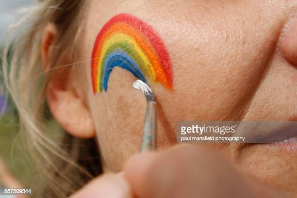 painting rainbow on adult ladies face - face paint stock pictures, royalty-free photos & images