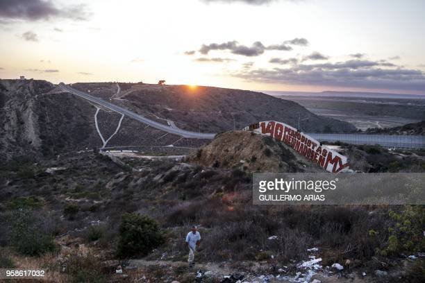 TOPSHOT A painting reading in Spanish 140 periodistas asesinado en MX is seen at a US/Mexico border fence section in Tijuana Baja California State...
