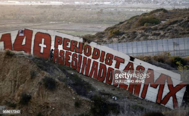 A painting reading in Spanish 140 periodistas asesinado en MX is seen at a US/Mexico border fence section in Tijuana Baja California State Mexico on...