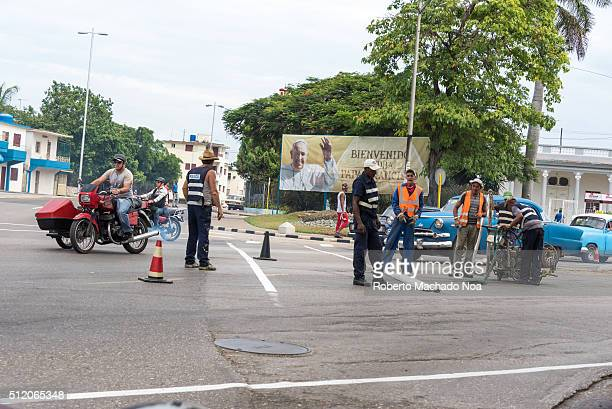 Painting streets preparations for Pope Francis visit Vintage cars go by and older motorcycles with sidecars workers wearing refreshing clothing like...