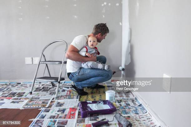 painting the playroom with baby. - bricolage humour photos et images de collection