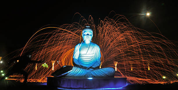 Painting with light photography burning steel wool creating circles of fire around statue of Buddha on the occasion of Buddha Purnima at Buddha...