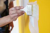 Painting with white paint over a yellow wall