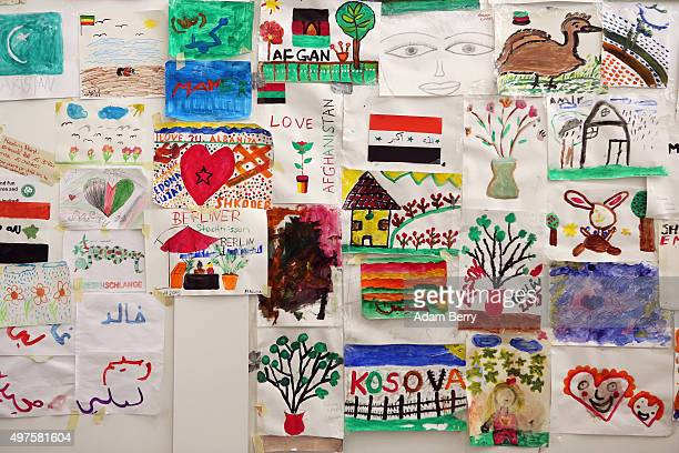 Paintings by child refugees hang in an airdome used as a temporary shelter for refugees on September 26 2015 in Berlin Germany Following the attacks...