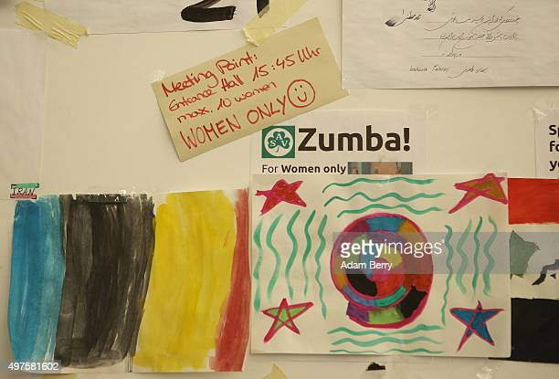 Paintings by child refugees hang under an announcement for a women's only Zumba class in an airdome used as a temporary shelter for refugees on...
