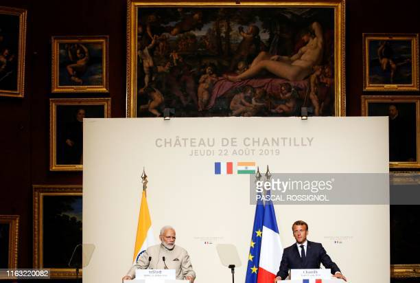 Paintings from the Chateau of Chantilly's art collection are seen in the background as French President Emmanuel Macron and Indian Prime Minister...