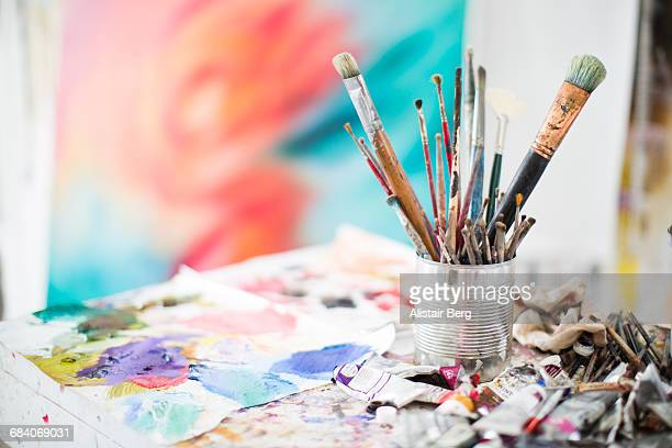 paints and paint brushes in an artists studio - paintbrush stock pictures, royalty-free photos & images