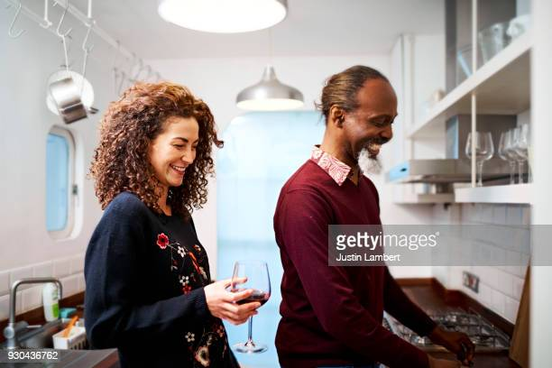 pair cooking together in the kitchen enjoying a joke and a moment together - adults only stock pictures, royalty-free photos & images