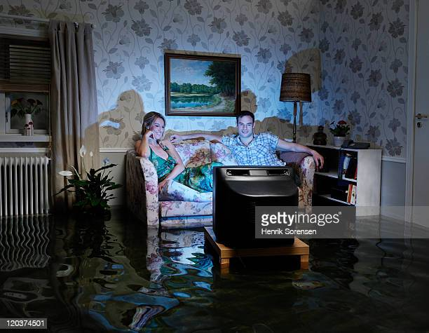 pair in front of TV in flooded room