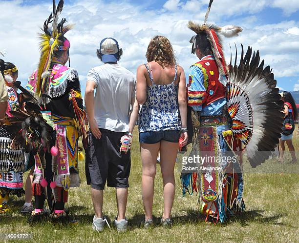 A pair of anglo visitors to the annual Taos Pow Wow pose for a photo with a group of NativeAmerican dancers The annual summer event in Taos Pueblo...