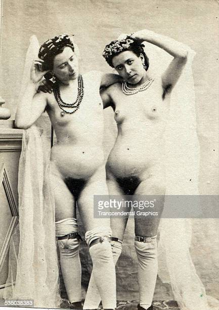 A pair of artists models wearing only necklaces hair pieces and leggings pose in an unknown photo studio in Paris France around 1860