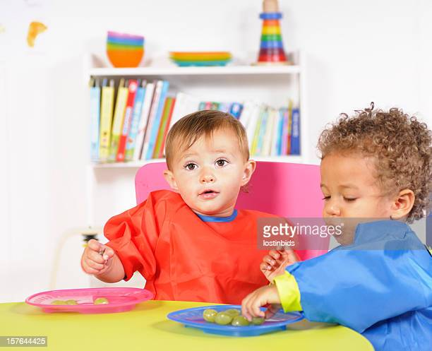 Pair Of Babies Eating Grapes In A Nursery Setting