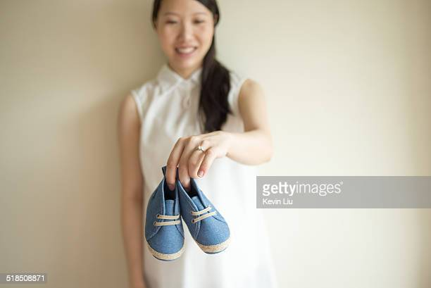 A pair of baby shoes held by a mother-to-be